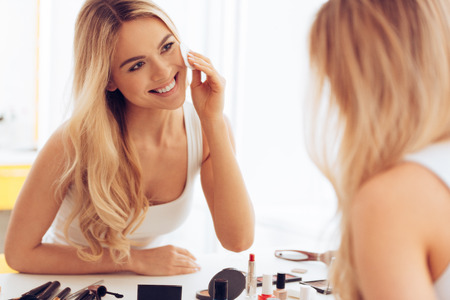 hair product: Taking off her make-up. Beautiful cheerful young woman using cotton disk and looking at her reflection in mirror with smile while sitting at the dressing table