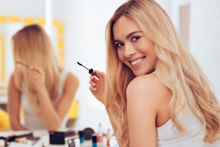 dressing table: I will be ready in five minutes! Beautifulyoung womanholding mascara and looking at camera with smile while sitting at the dressing table