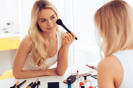 loves: She loves what she sees in the mirror. Beautiful young woman applying make-up and looking at her reflection in mirror while sitting at the dressing table Stock Photo