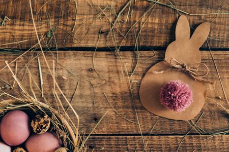 cor: Ester Bunny. Top view of colored Easter eggs in bowl with hay and Easter bunny made from brown paper lying on wooden rustic table