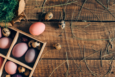 cor: Getting ready for Easter. Top view of Easter eggs in wooden box and plant lying on wooden rustic table with hay