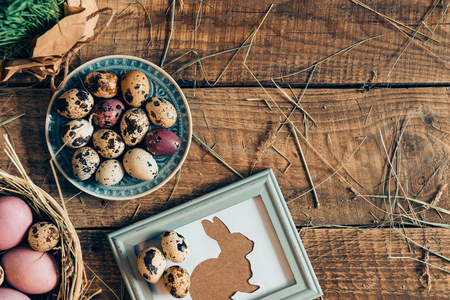 d cor: Easter table. Top view of Easter eggs on plates and Easter rabbit in picture frame lying on wooden rustic table with hay