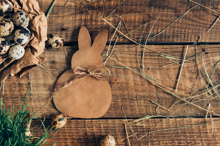Organic Easter. Top view of quail eggs in crumpled brown paper and ester bunny lying on wooden rustic table
