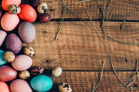 cor: Colorful eggs. Top view of colored Easter eggs lying on wooden rustic table Stock Photo
