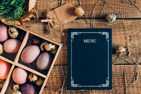 d cor: Easter menu. Top view of Easter eggs in wooden box and menu board lying on wooden rustic table with hay Stock Photo