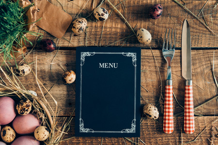 Easter dinner menu. Top view of Easter eggs and menu board with fork and knife lying on wooden rustic table with hay