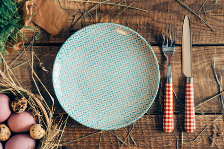 cor: Easter dinner. Top view of Easter eggs in bowl and plate with fork and knife lying on wooden rustic table with hay