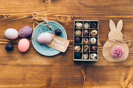 d cor: Easter vibes. Top view of colored Ester eggs on plate and Easter decorations lying on wooden rustic table Stock Photo
