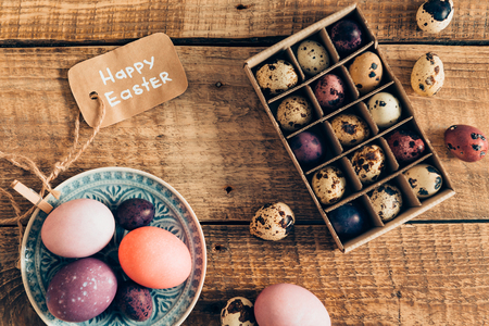 cor: Easter decor. Top view of colored Easter eggs on plate and Easter quail eggs in box lying on wooden rustic table