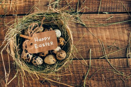 easter eggs: Organic Easter. Top view of quail eggs lying in bowl with hay with Easter label on wooden rustic table