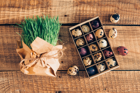 cor: Preparation to Easter. Top view of grass package and box of Easter quail eggs lying on wooden rustic table Stock Photo