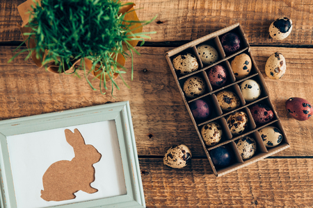 cor: Spring holidays. Top view of Easter bunny in picture frame and box of Easter quail eggs lying on wooden rustic table Stock Photo