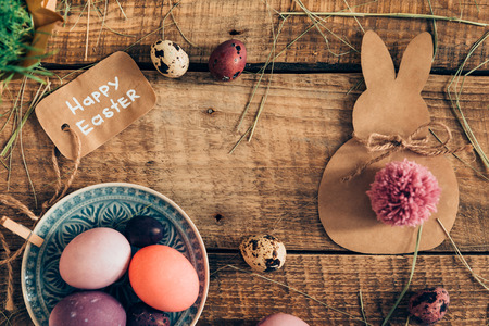 d cor: Happy Ester! Top view of colored Easter eggs and Easter decorations lying on wooden rustic table Stock Photo