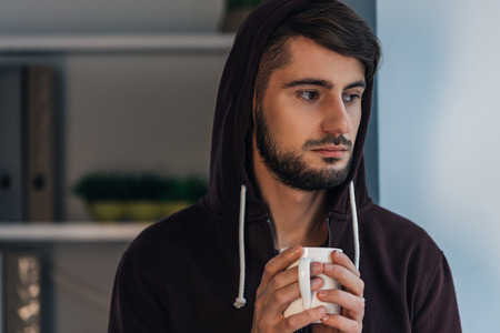 hooded shirt: Feeling frustrated. Portrait of pensive young man in hooded shirt holding coffee cup and looking away while standing at home