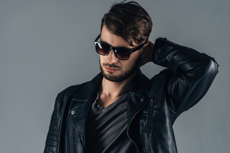 men standing: Trendy look. Confident young man in sunglasses looking down while standing against grey background