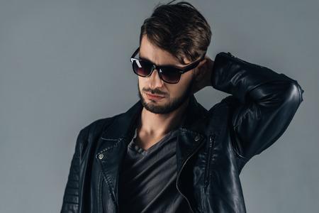 Trendy Look. Zuversichtlich junger Mann mit Sonnenbrille nach unten, während die grauen Hintergrund gegen Standard-Bild