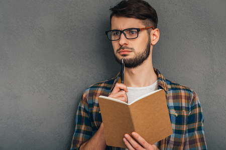 What shall I write?Pensive young man in sunglasses holding notebook and looking away while standing against grey background