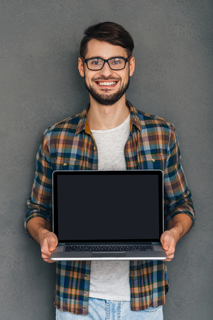 poner atencion: Pay attention to this! Confident young man showing his laptop and looking at camera with smile while standing against grey background Foto de archivo
