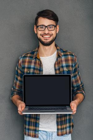 poner atencion: Prestar atención a esto! Seguro de joven que muestra su portátil y mirando la cámara con una sonrisa mientras está de pie contra el fondo gris Foto de archivo