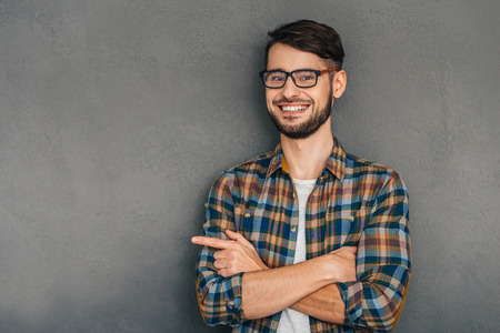 This is my choice! Cheerful young man in glasses pointing at copy space and looking at camera with smile while standing against grey background Stock Photo