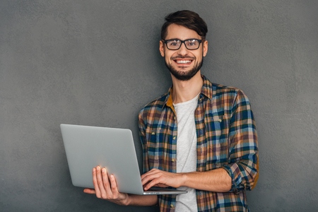 background person: Ready to help you. Confident young man holding his laptop and looking at camera with smile while standing against grey background