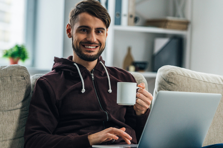 net surfing: Surfing net at home. Cheerful young man using his laptop and looking at camera with smile while sitting on couch at home Stock Photo