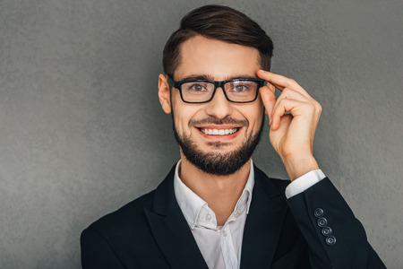 I clearly can see this! Portrait of cheerful young man looking at camera with smile and adjusting his glasses while standing against grey background