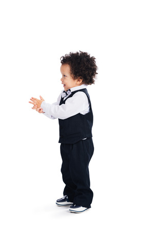 toddler boy: Cute baby boy. Side view of little African baby boy looking away with smile while standing against white background Stock Photo