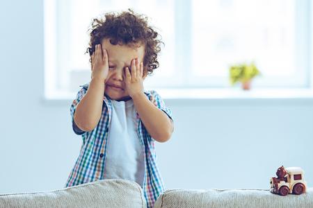 ¡Oh no! Poco niño africano llorando y frotándose los ojos mientras está de pie en el sofá en casa