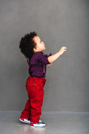 Fangen wir mit mir gehen! Seitenansicht des kleinen afrikanischen Baby, Wegschauen und streckte seine Hand aus, während, die gegen grauen Hintergrund