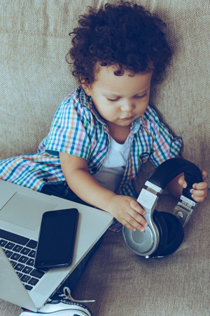 I really need all this gadgets! High angle view of little African baby boy holding headphones while sitting on the couch at home with laptop and smartphone on his knees