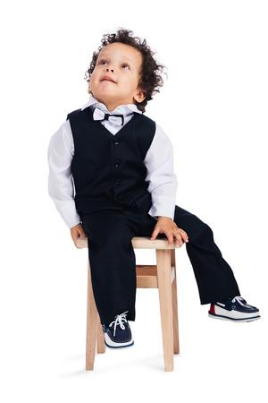 bebe sentado: Es que una araña en el techo? Poco niño africano que mira para arriba mientras que se sienta en taburete contra el fondo blanco