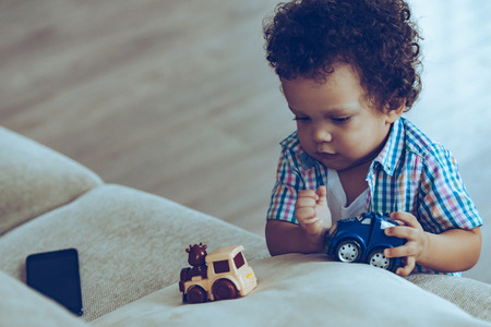 baby boys: Boys love little trains. Little African baby boy playing with toys while standing near the couch at home Stock Photo