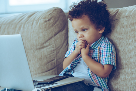What else to do? Little African baby boy looking at his laptop and biting his nails while sitting on the couch at home Stock Photo