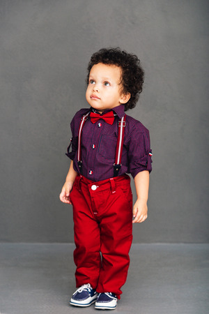 I am ready for a date! Little African baby boy looking away while standing against grey background