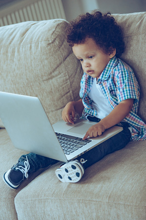 looking at baby: How dad uses this thing? High angle view of little African baby boy using his laptop while sitting on the couch at home Stock Photo