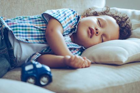 Dulces sueños. Poco niño africano de dormir mientras está acostado en el sofá en casa Foto de archivo