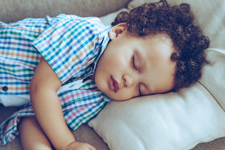 toddler boy: Sweet dreams. Little African baby boy sleeping while lying on couch at home Stock Photo