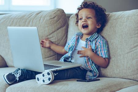 persona feliz: Madre cómo hace esta cosa se enciende? Poco niño africano manteniendo la boca abierta mientras se está sentado en el sofá en casa con el ordenador portátil sobre sus rodillas