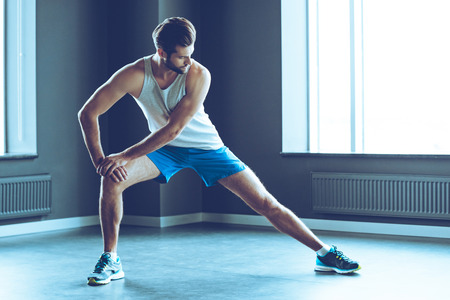 only one person: Stretching after great work out. Young handsome man in sportswear doing stretching at gym Stock Photo