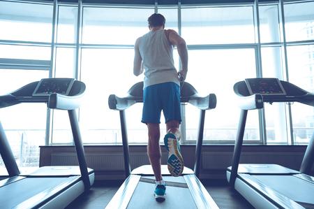 Jogging zijn weg naar een goede gezondheid. Full-length achteraanzicht van jonge man in sportkleding die op loopband voor venster in sportschool loopt Stockfoto