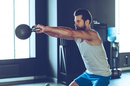 salud y deporte: entrenamiento cruzado intensiva. Vista lateral de joven guapo en ropa deportiva con la campana hervidor de agua en el gimnasio
