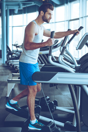 Getting the best body. Full length side view of young handsome man in sportswear looking away while working out on stepper at gym Stock Photo
