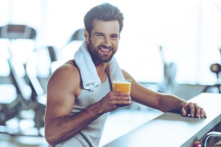 tomando jugo: Sip de frescura después de un gran entrenamiento. Vista lateral de apuestos jóvenes en ropa deportiva de retención de vidrio de zumo de naranja y mirando a cámara con una sonrisa mientras se está sentado en el mostrador de la barra en el gimnasio