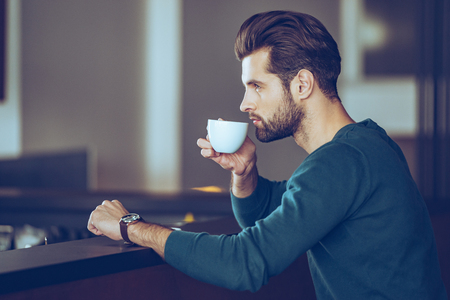 side bar: Nothing better then cup of fresh espresso. Side view of handsome young man drinking coffee while sitting at bar counter