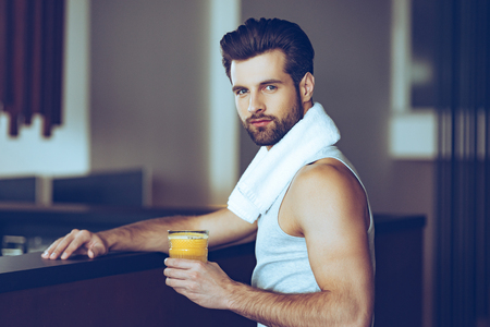 juice bar: Orange juice after great workout. Side view of handsome young men in sportswear holding glass of fresh orange juice and looking at camera while sitting at bar counter at gym