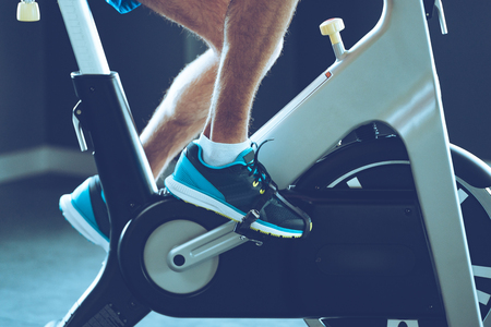 Intense cardio workout. Side view close-up part of young man in sports shoes cycling at gym Reklamní fotografie