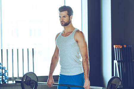 hombre deportista: atleta concentrado. Hombre hermoso joven en ropa deportiva barra de elevación en el gimnasio