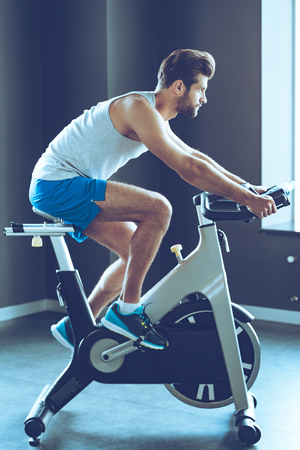 man gym: His favorite cardio workout. Side view full length of young handsome man in sportswear cycling at gym