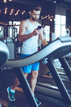 treadmill: Great song for his exercising. Full length of young handsome man in sportswear using his smart phone while walking on treadmill at gym Stock Photo